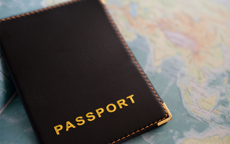 Black passport with map in the background